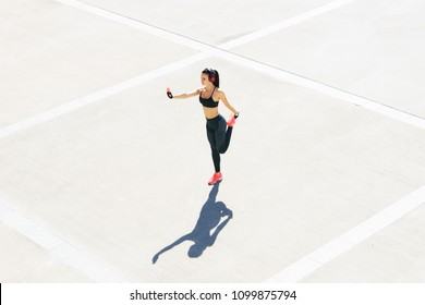 Young, fit and sporty girl in the street. Fitness, sport, urban jogging and healthy lifestyle concept.