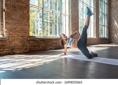 Young fit sporty healthy active woman wear sportswear lying on mat in side plank pose leg up do yoga fitness training workout stretch exercise concept on wooden floor in modern sunny gym space indoor.