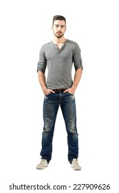 Young fit standing man with hands in pocket. Full body length portrait isolated over white background.