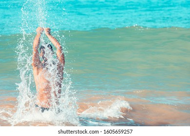 Young, fit and tanned man playing in the waves of a turquoise sea. Vacation and holiday concept. Copy space on the right.