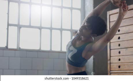 young fit and tone up woman doing heating before a fitness workout in sunny loft running in place and streatching