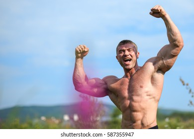 Young fit topless bodybuilder outdoors demonstrating muscles, strong body, six pack abs, copy space for text
