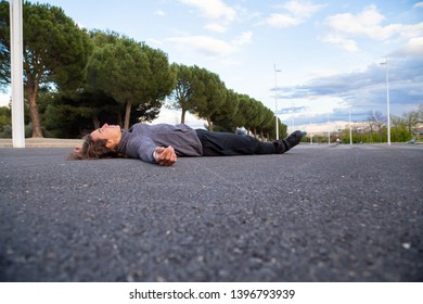 Young fit weary man in sportswear with roller skates lying on road in beautiful city park
