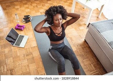 Young fit woman in black sportswear is doing sit-ups at home. Slim sporty girl doing v-ups abs workout at home. Healthy fit young woman in activewear sitting on mat in living-room and doing sit-ups