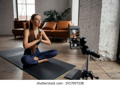 Young fit woman blogger meditation and recording online translation by phone. Live concept