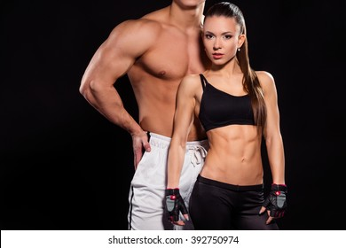 Young fit woman and bodybuilder. Couple of fitness models. Modern art of bodybuilding. Trainer and his student.