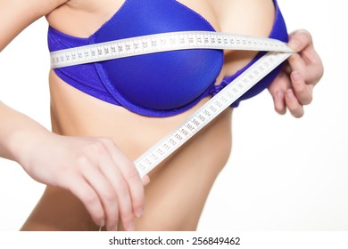 Young fit woman checking her breast measurement. Over white background