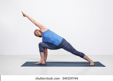 Young fit woman doing Ashtanga Vinyasa Yoga asana Utthita parsvakonasana - extended side angle pose advanced variation