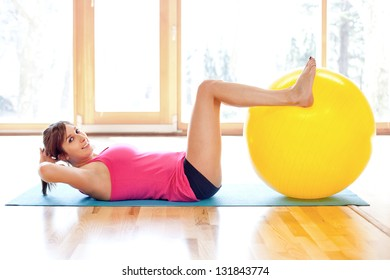 Young fit woman doing exercises with fitness ball