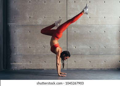 Young fit woman doing handstand exercise in studio.