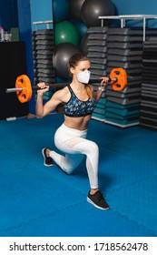 Junge passte Frau, die im Fitnessraum Lunges mit einer n95 Gesichtsmaske macht. Fitness-Training mit Gewichten unter Covid-19 Gesundheitskrise.