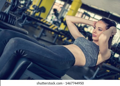 Young fit woman doing situps on exercise bench in gym