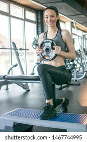 Young fit woman doing squats with weight plate on stepper platform in gym