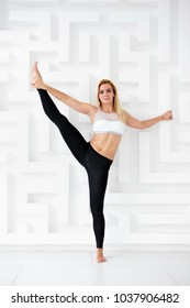 Young fit woman doing a stretching exercise near white wall at fitness studio. Utthita Hasta Padangusthasana pose