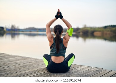 Young fit woman doing yoga outdoor near the lake