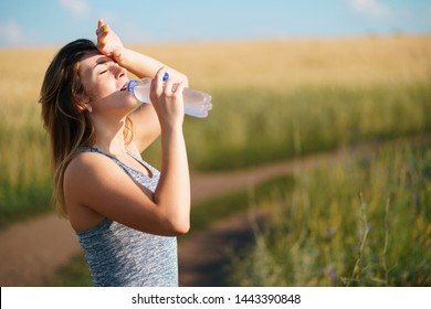 Young fit woman drink water after outdoor jogging. Morning training, fitness, healthy lifestyle
