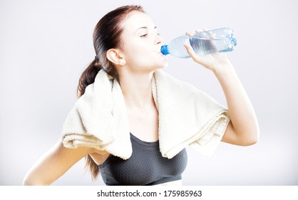 Young fit woman drinking water after fitness training