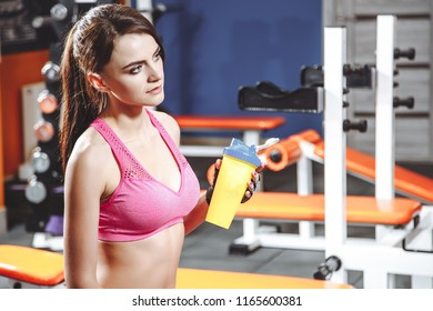Young fit woman with energy drink relaxing and drinking in the gym. Sport and fittness concept.