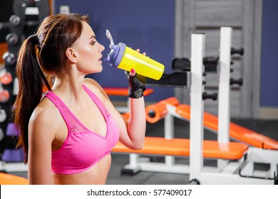 Young fit woman with energy drink relaxing and drinking in the gym. Sport and fittness concept