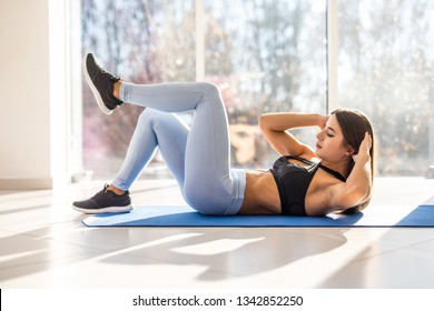 Young fit woman exercising in gym lying on mat doing leg raising and twisting exercises. Young attractive woman doing abs workout. Fitness woman doing a sit up.