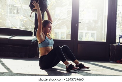 Young fit woman exercising with heavy ball at gym