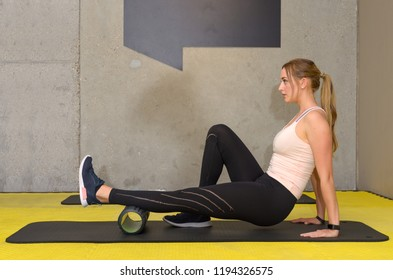 Young fit woman exercising legs using foam roller at gym
