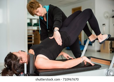 Young fit woman exercising on pilates device reformer with female instructor at empty gym. Sports equipment. Goals and motivation