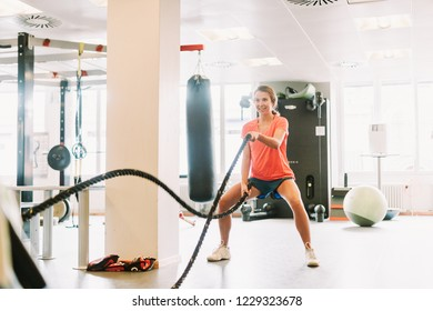 Young fit woman exercising with rope at gym
