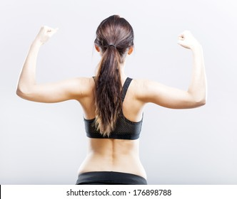 Young fit woman flexing her biceps, back view