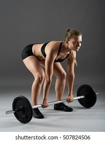 Young fit woman with heavy barbell doing deadlift for back workout