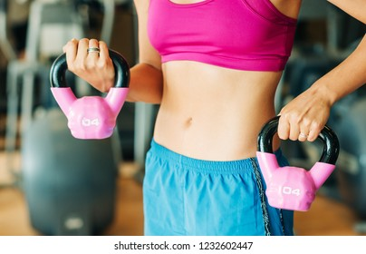 Young fit woman holding pink 4 kg barbells, close up image of female waist, health and sport lifestyle