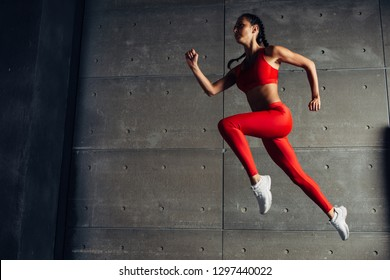 Young fit woman jumping while running Fitness sport girl exercising.