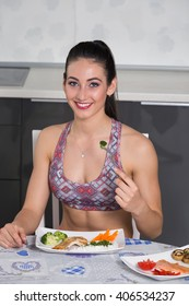 young fit woman in the kitchen, with two plates of healthy food: rice, chicken grill, broccoli, carrots, mushrooms, salmon, tomato, red peppers