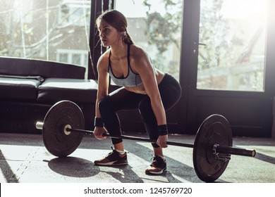 Young fit woman lifting heavy weights in gym