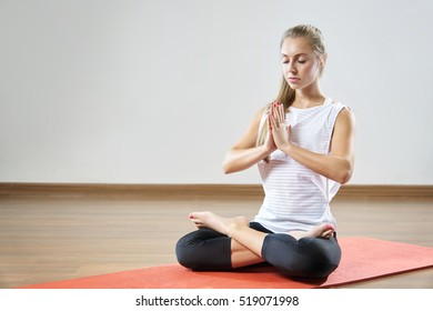 Young fit woman is meditating in the fitness class