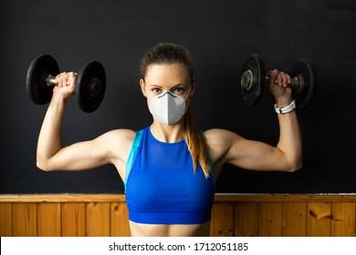 Junge passte Frau mit n96 Gesichtsmaske, die Schulterpresse im Fitnessraum mit Hantel ausübt. Fitness-Krafttraining unter der Gesundheitskrise durch das Koronavirus.