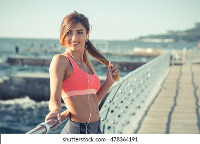 Young fit woman on the pier in sports bra