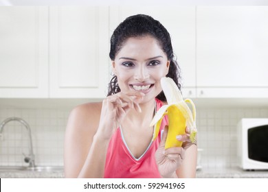Young fit woman peeling and eating a ripe banana in the kitchen