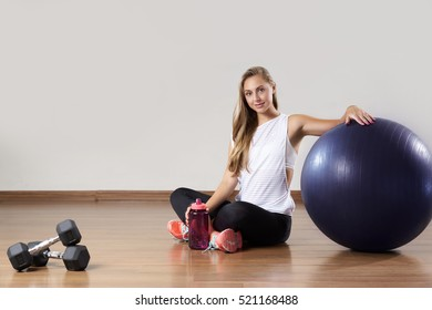 Young fit woman relaxes after training near gymnastic ball