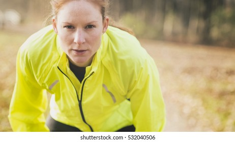 Young fit woman resting during a morning run in a park.