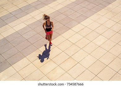Young fit woman running in sunny day in the city fill active girl.