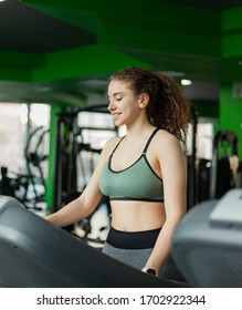 Young fit woman in sportswear before basic training runs on a treadmill in the gym. The concept of a healthy lifestyle, warming up, fitness.