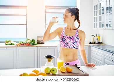 Young fit woman in sportswear drinking water while standing at kitchen.