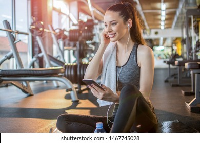 Young fit woman in sportswear with earphones listening to music on her smart phone and taking a rest on fitness mat after gym workout.