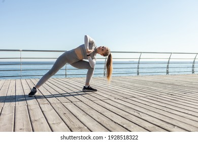 Young fit woman in sportswear practices yoga asana pose on the beach on a bright sunny day.