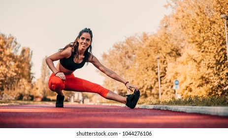 Young fit woman stretching on tartan track before run.