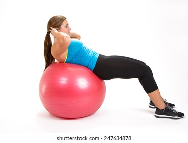 Young fit woman stretching on ball in a sit up position.