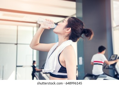 Young fit woman with towel drinking water in the gym. Sport and fitness concept