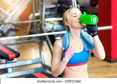 Young fit woman with towel and energy drink relaxing and drinking in the gym. Sport and fittness concept