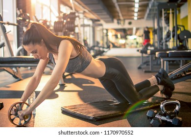 Young fit woman training with abs wheel roller at gym